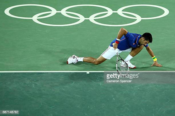 Novak Djokovic of Serbia stumbles during his match against Juan Martin Del Potro of Argentina in their singles match on Day 2 of the Rio 2016 Olympic...