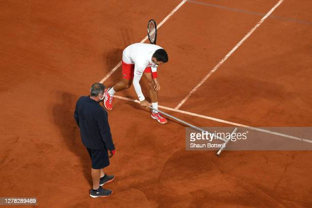 Novak Djokovic of Serbia sweeps the court as a member of staff looks on during his Men's Singles third round match against Daniel Elahi Galan of...