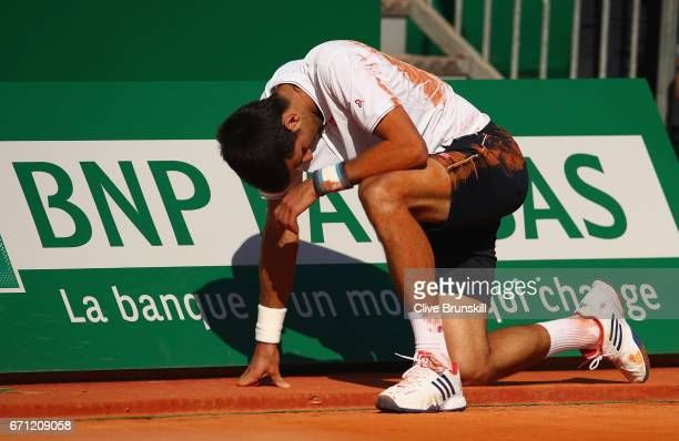 Novak Djokovic of Serbia takes a minute to get up after falling over against David Goffin of Belgium in their quarter final round match on day six of...