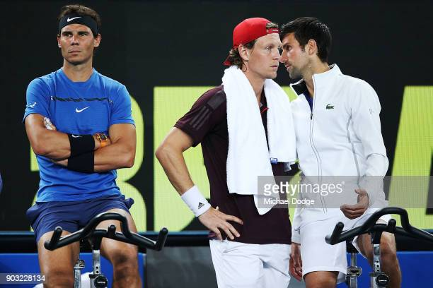 Novak Djokovic of Serbia talks to Tomas Berdych of the Czech Repblic next to Rafael Nadal of Spain hits a backhand during the Tie Break Tens ahead of...