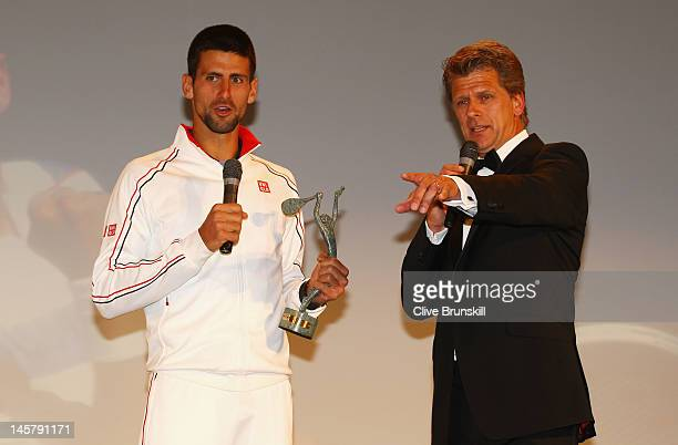 Novak Djokovic of Serbia talks with Andrew Castle after receiving the Men's Singles World Champion award during the ITF World Champions Dinner at...