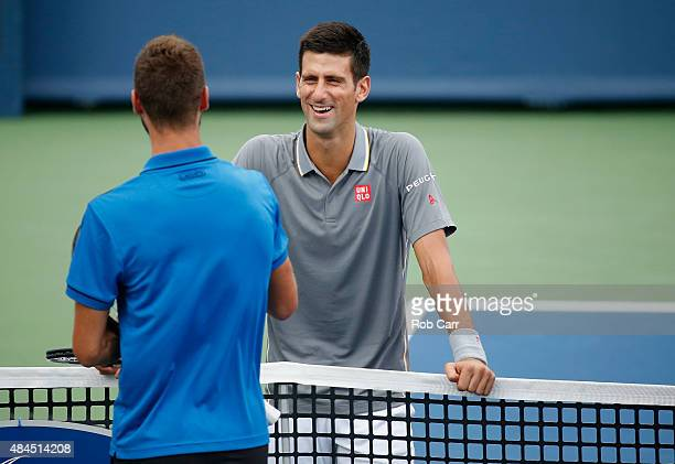 Novak Djokovic of Serbia talks with opponet Benoit Paire of France during a rain delay in the start of their match during the Western Southern Open...