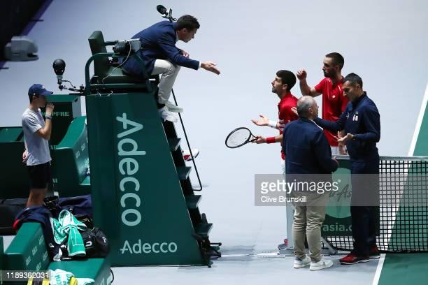 Novak Djokovic of Serbia, team mate Viktor Troicki, Coach Nenad Simic and Tournament Referee Wayne McKewen talk to the umpire during their quarter...