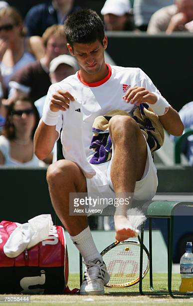 Novak Djokovic of Serbia tends to a foot injury during the Men's Singles semifinal match against Rafael Nadal of Spain during day twelve of the...