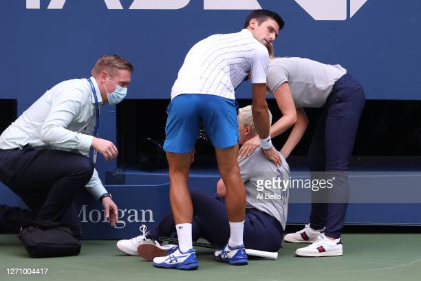 Novak Djokovic of Serbia tends to a line judge Laura Clark who was hit with the ball during his Men's Singles fourth round match against Pablo...