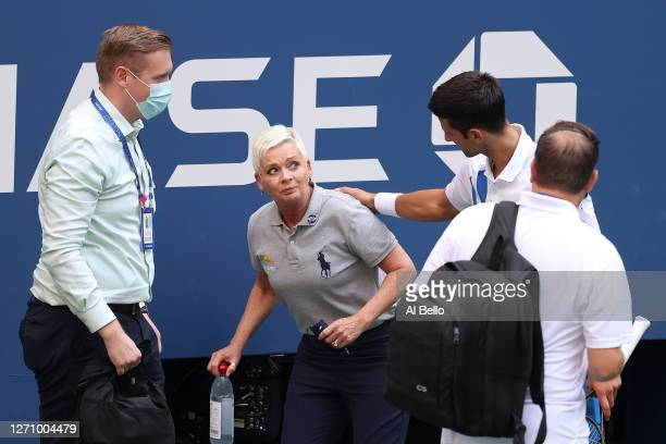 Novak Djokovic of Serbia tends to a lineswoman Laura Clark after inadvertently striking her with a ball hit in frustration during his Men's Singles...