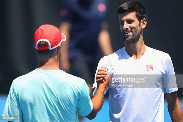 Novak Djokovic of Serbia thanks Omar Jasika of Australia for hitting up during their practice session ahead of the 2017 Australian Open at Melbourne...