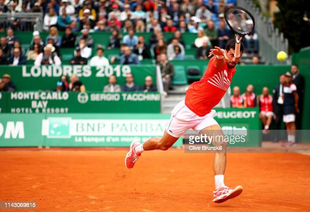 Novak Djokovic of Serbia throws his racket at the ball after trying to play a backhand against Philipp Kohlschreiber of Germany in their second round...