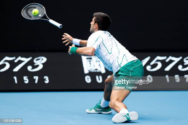 Novak Djokovic of Serbia throws his racquet to attempt to return the ball during his Men's Singles second round match against Tatsuma Ito of Japan on...