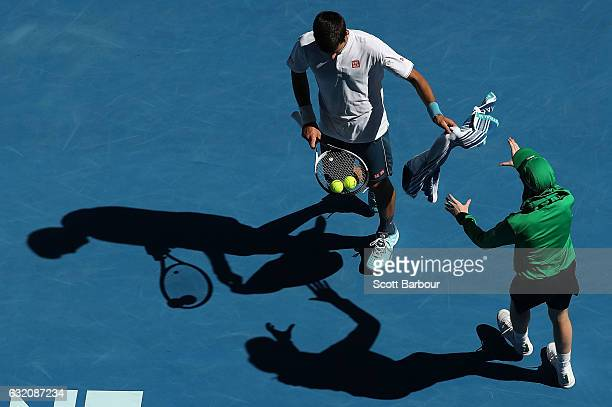 Novak Djokovic of Serbia throws his towel back to a ball kid in his second round match against Denis Istomin of Uzbekistan on day four of the 2017...