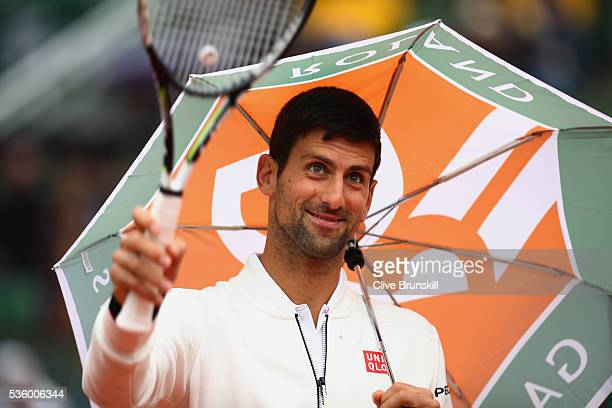 Novak Djokovic of Serbia walks back onto court following a rain delay during the Men's Singles fourth round match against Roberto Bautista Agut of...