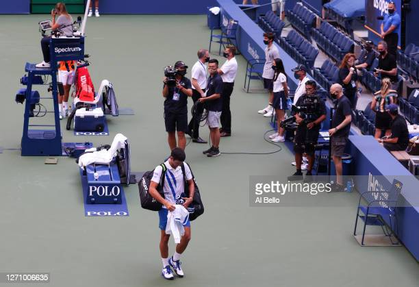 Novak Djokovic of Serbia walks off the court after being defaulted due to inadvertently striking a lineswoman Laura Clark with a ball hit in...