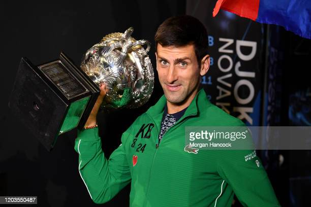 Novak Djokovic of Serbia walks onto Margaret Court Arena holding the Norman Brookes Challenge Cup after winning the Men's Singles Final against...