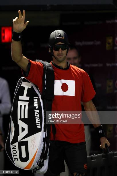 Novak Djokovic of Serbia walks out on to the court wearing a tshirt for Japan Relief prior to his match against Denis Istomin of Uzbekistan of during...