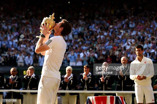 Novak Djokovic of Serbia watches Andy Murray of Great Britain as he kisses the Gentlemen's Singles Trophy following his victory in the Gentlemen's...