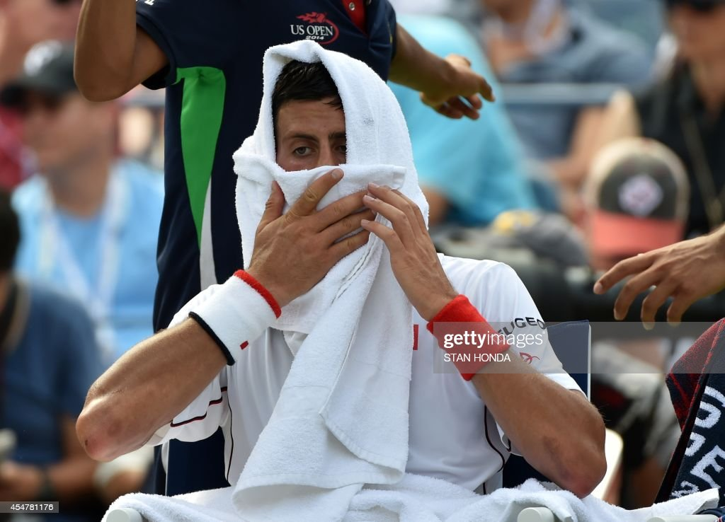 Novak Djokovic of Serbia wipes his face during a break in play against Kei Nishikori of Japan during their 2014 US Open men's semifinal singles match at the USTA Billie Jean King National Tennis Center September 6, 2014 in New York. AFP PHOTO/Stan HONDA /