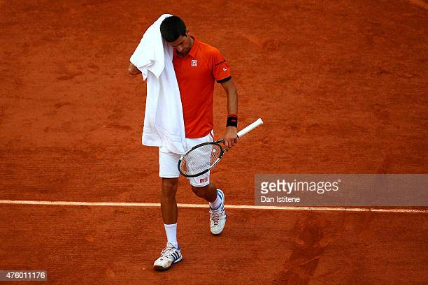 Novak Djokovic of Serbia wipes his face with a towel in his Men's Semi Final match against Andy Murray of Great Britain on day thirteen of the 2015...