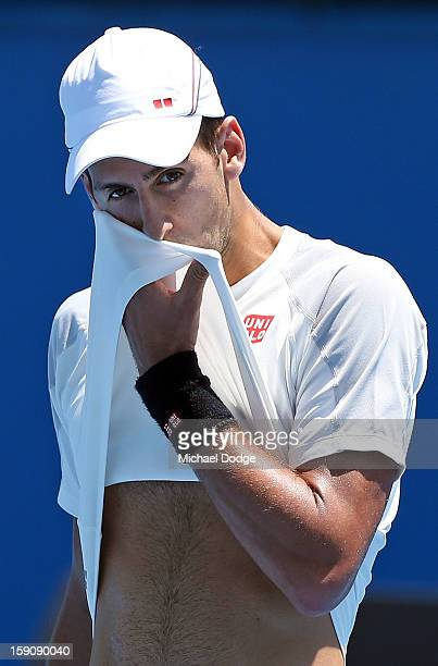 Novak Djokovic of Serbia wipes sweat of his face during practice ahead of the 2013 Australian Open at Melbourne Park on January 8 2013 in Melbourne...