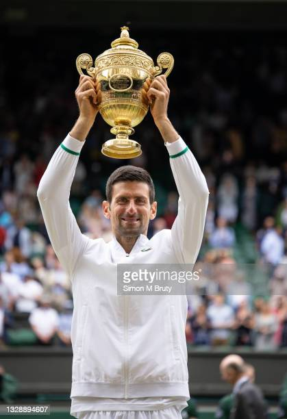 Novak Djokovic of Serbia with the trophy after victory in the Men's Singles Final against Matteo Berrettini of Italy at The Wimbledon Lawn Tennis...