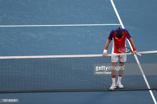 Novak Djokovic of Team Serbia waits at the net to congratulate Pablo Carreno Busta of Team Spain on his victory after their Men's Singles Bronze...