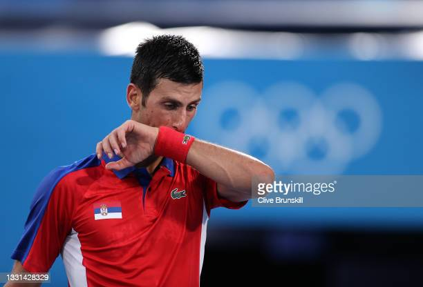 Novak Djokovic of Team Serbia wipes away sweat during his Men's Singles Semifinal match against Alexander Zverev of Team Germany on day seven of the...