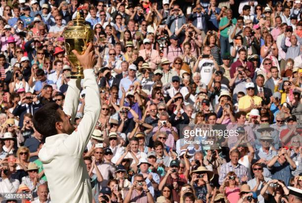 Novak Djokovic poses with the winners trophy after beating Roger Federer on centre court during the mens singles final of the Wimbledon Championships...