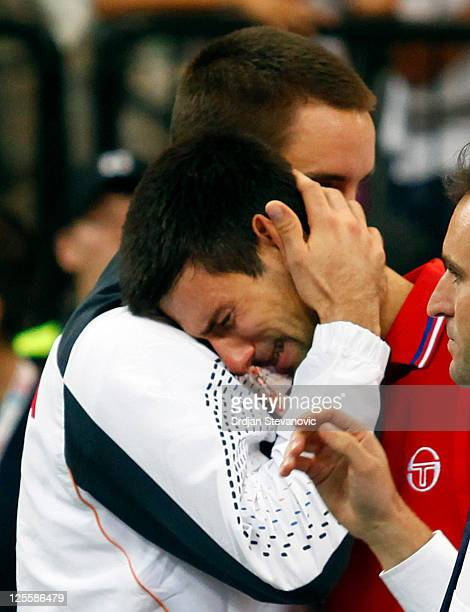 Novak Djokovic reacts after retiring from a match against Juan Martin Del Potro of Argentina during the Davis Cup singles semi final match between...