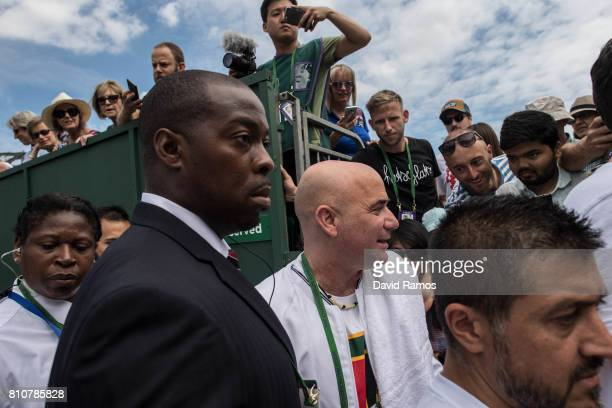 Novak Djokovic's coach Andre Agassi walk past tennis fans after a training session of Novak Djokovic on day six of the Wimbledon Lawn Tennis...