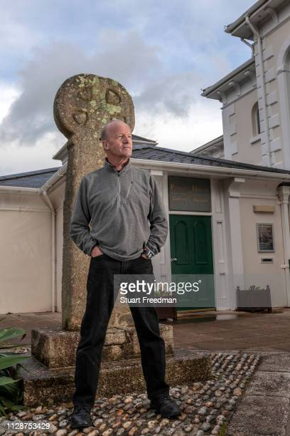Novelist author and journalist Jim Crace stands by the Celtic Cross at the Penlee House Gallery Penzance United Kingdom