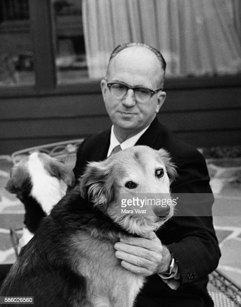 Novelist James Michener pets one of his dogs while the other looks away on a patio Michener is well known for his epic novels usually inspired by a...