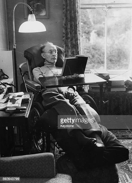 Novelist Joyce Cary reading a book in a special wheelchair for his Motor Neuron Disease August 24th 1956