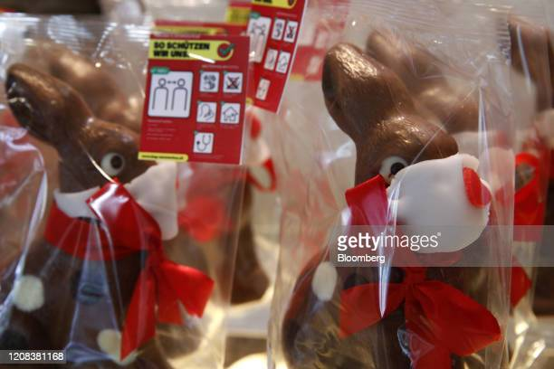 Novelty chocolate easter bunnies with face mask decorations and a label containing coronavirus advice stand on display at Baeckerei Bohnenblust...