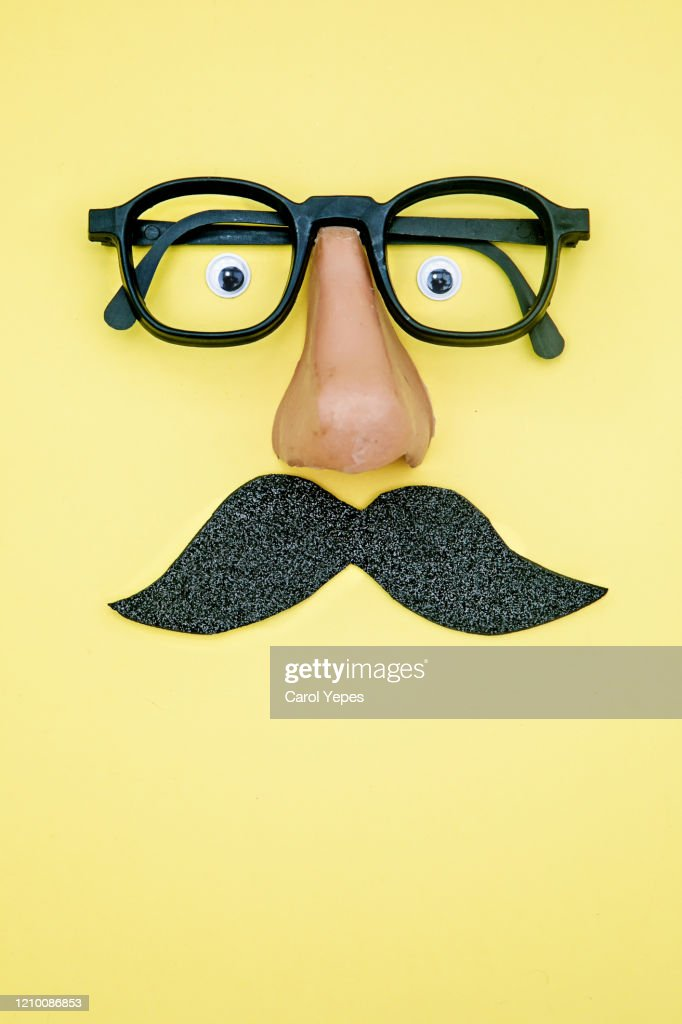 novelty glasses with fake moustache and googly eyes.Yellow background : Stock Photo