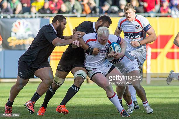 Eagles prop forward Eric Fry is tackled by New Zealand All Blacks prop Charlie Faumuina and lock Patrick Tuipulotu during the game between the New...