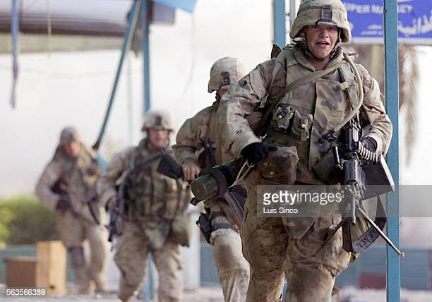November 10th 2004––Fallouja Iraq––Marines run back to the Al Hadra Mosque after sniper fire on Wednesday slowed their advance on a mosque where...