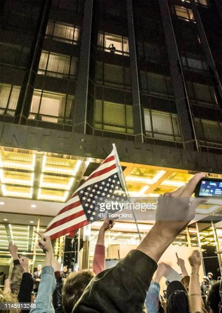 Protesters outside of Trump Plaza give the middle finger to a tenant in the uilding looking down at the rally on November 11 2016 in New York City