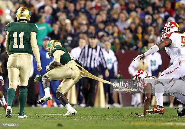 Shaquan Virgil of the University of Maryland pulls on the pants of Jonas Gray of the University of Notre Dame during an NCAA game at Fedex Field in...