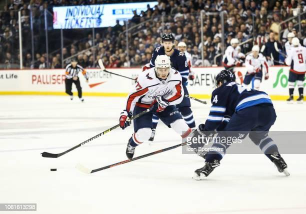 Washington Capitals forward TJ Oshie skates in on Winnipeg Jets defenseman Josh Morrissey during the regular season game between the Winnipeg Jets...