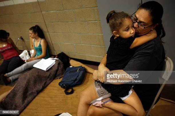 November 15 2008 Katrina Vieane hugs her 4–year–old daughter Briana Burgeno at a temporary shelter set up for evacuated residents at John F Kennedy...