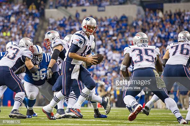 New England Patriots quarterback Tom Brady drops back to hand off to New England Patriots running back Jonas Gray during a football game between the...