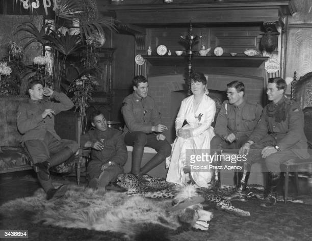 Resting her feet on bearskin and leopardskin rugs, Madam Ada Crossly chats with the wounded Anzacs whom she has come to entertain during World War I.