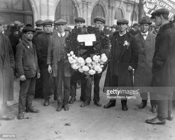 A wreath from the 'Camberwell Organised Unemployed' being presented on Armistice Day Some of the men are wearing pawn tickets behind their medals
