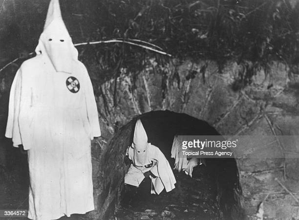 Members of the American white supremecist movement the Ku Klux Clan crawling out of a tunnel after a meeting