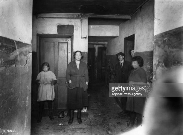 A group of people in the entrance of a tenement house in Lismore Street Bethnal Green east London