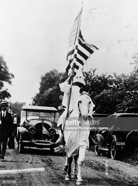 A member of the Ku Klux Klan carrying an American flag during a klan parade in Niles Ohio