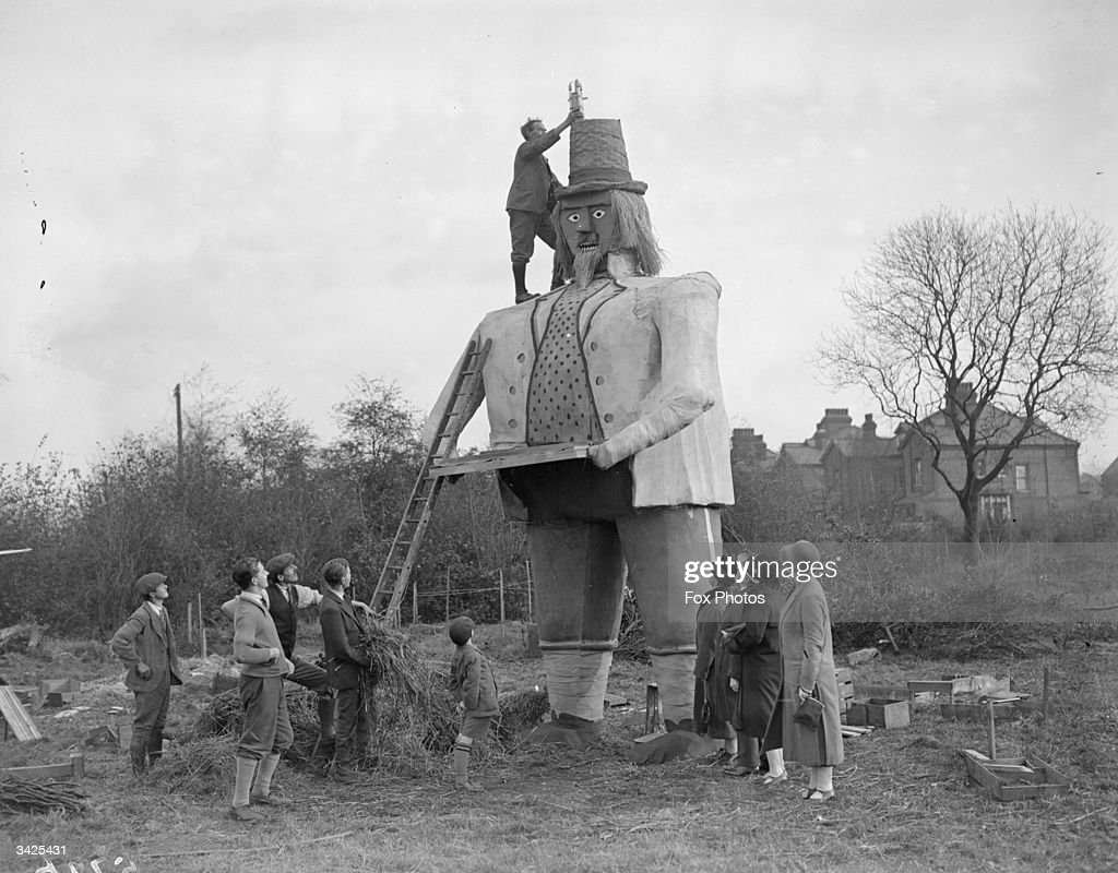 Mr C W Clarke putting a rocket on the hat of his 23ft Guy Fawkes which weighs 3 tons, watched by villagers in Beckenham.