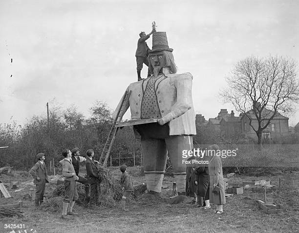 Mr C W Clarke putting a rocket on the hat of his 23ft Guy Fawkes which weighs 3 tons watched by villagers in Beckenham