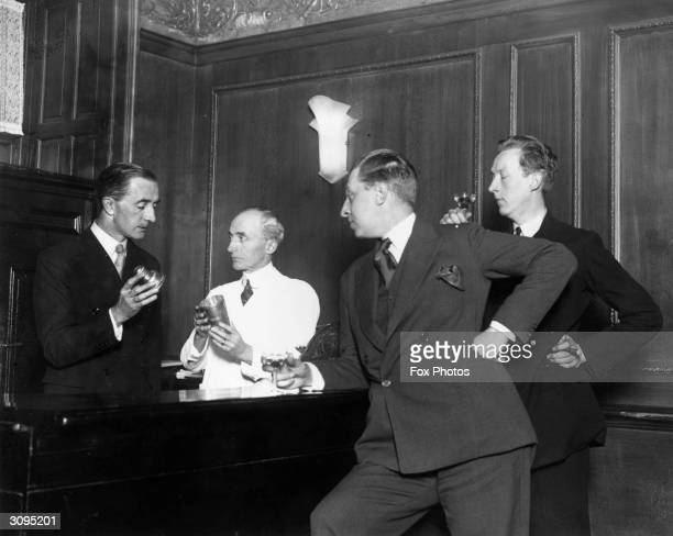 Writers and brothers Osbert and Sacheverell Sitwell watch Martyn Roland of the Savoy Hotel and Harry Craddock the barman demonstrate how to shake a...