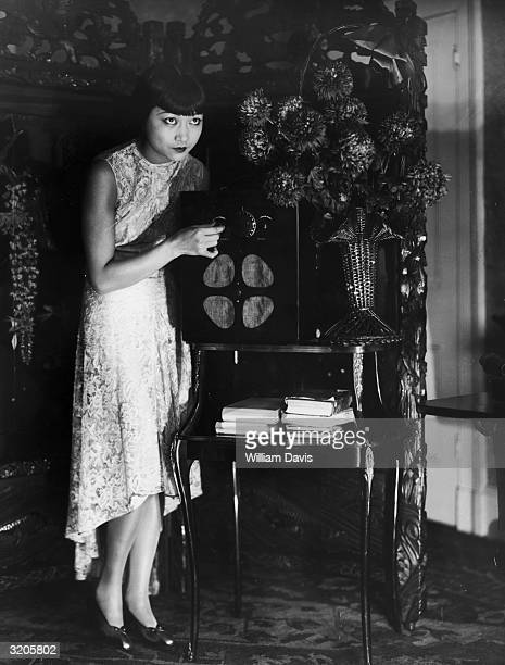 American film star Anna May Wong tunes in her wireless set at her flat in London