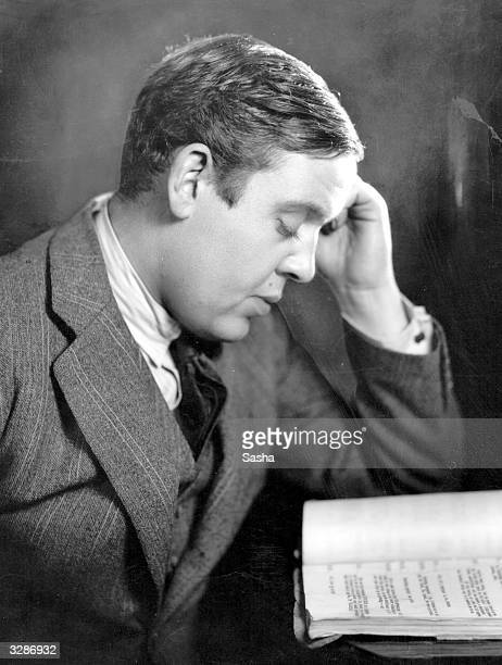 British character actor Charles Laughton sits at a desk reading for the part of 'Mr Pickwick' at the Haymarket Theatre